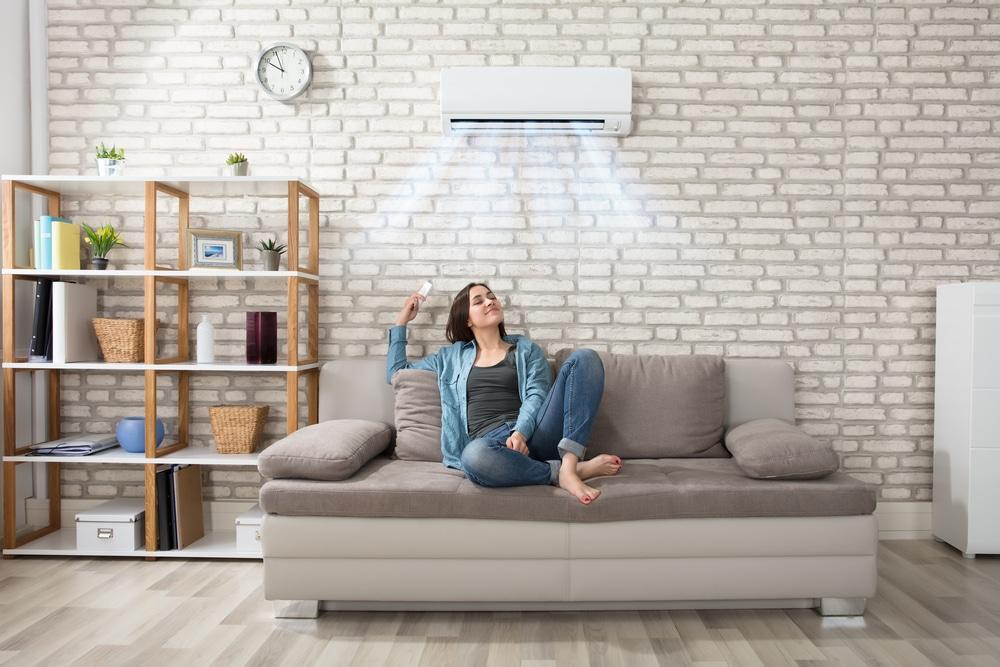 Kobieta obsługująca klimatyzator z oczyszczaczem powietrza